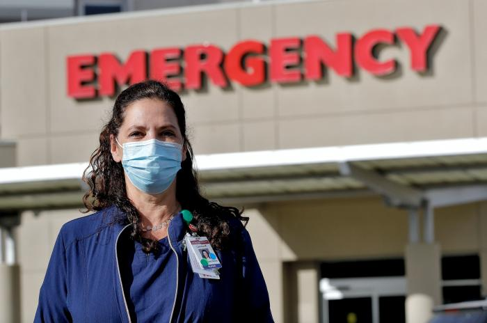 Caroline Maloney stands outside HonorHealth's Scottsdale Osborn Medical Center at the end of her overnight shift early Friday, June 26, 2020 in Scottsdale, Ariz.