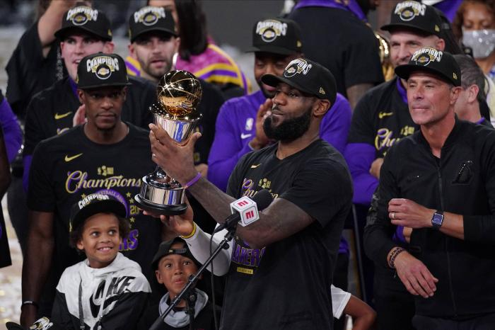 Los Angeles Lakers' LeBron James (23) holds the MVP trophy as he celebrates with his teammates after the Lakers defeated the Miami Heat 106-93 in Game 6 of basketball's NBA Finals Sunday, Oct. 11, 2020, in Lake Buena Vista, Fla. (AP Photo/Mark J. Terrill)