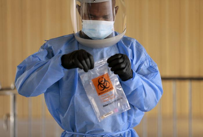 Divine Ayong seals a test in a biohazard bag after collecting a sample Monday, Sept. 21, 2020, at The University of Texas.
