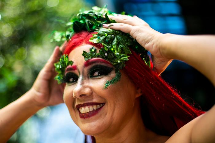 "A member of the ""Desliga da Justica"" street band get dressed in her costume in Rio de Janeiro, Brazil, Sunday, Feb. 14, 2021"