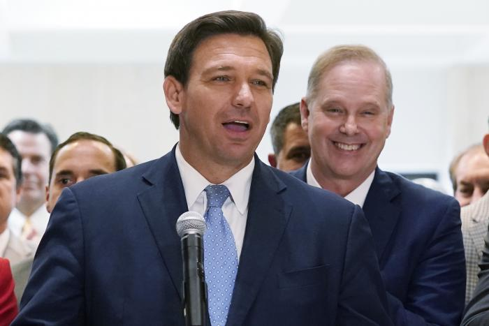 Surrounded by lawmakers, Florida Gov.Ron DeSantis speaks at the end of a legislative session at the Capitol in Tallahassee, Fla.