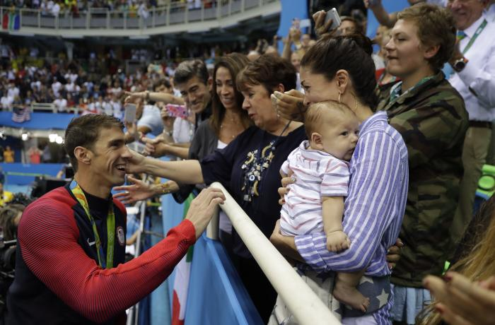 United States' Michael Phelps celebrates winning his gold medal in the men's 200-meter butterfly with his mother Debbie, fiance Nicole Johnson and baby Boomer during the swimming competitions at the 2016 Summer Olympics in Rio de Janeiro, Brazil.