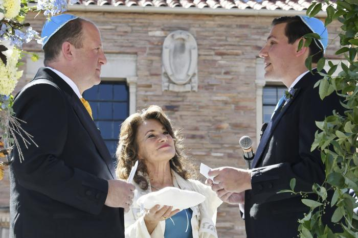 Rabbi Tirzah Firestone, center, officiates a traditional Jewish wedding ceremony attended by family and friends for Colorado Gov. Jared Polis, left, and his partner, Marlon Reis, in Boulder, Colo.
